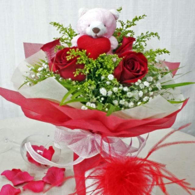 6 red roses with bear at centre.
