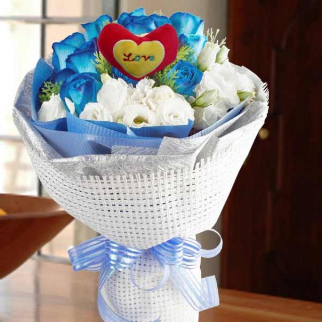 12 Blue Roses with heart shape Tag at centre.