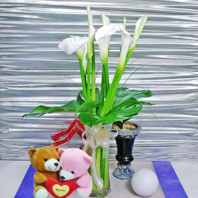 9 Cala-Lilies in a vase with a pair of Bears