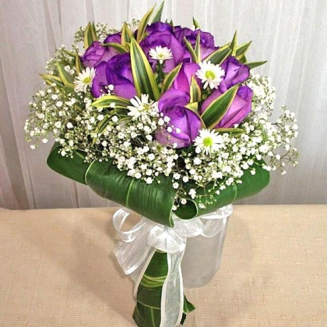 12 purple Roses, White phoenix wrap with Dracaena foliage.