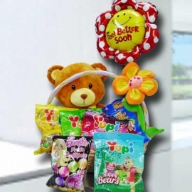 12inch bear sits in a basket, surrounded with sweets and a balloon